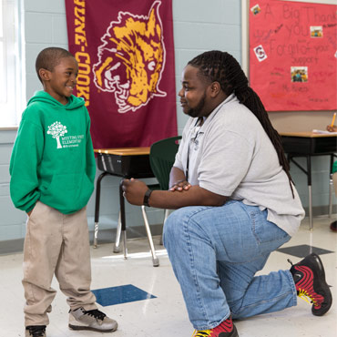 teacher in a grey shirt kneeling talking to a smiling young boy wearing a green hoodie