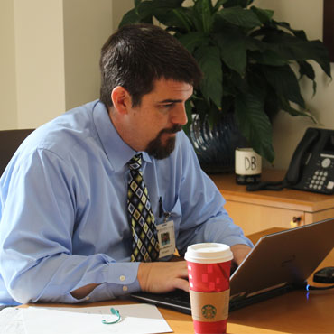 man sitting at a desk working on a laptop