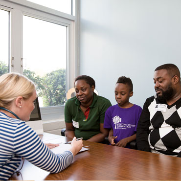 Parents with their young child meeting with school staff
