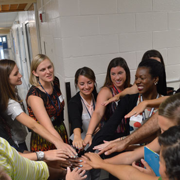 group of teachers with their hands in a huddle