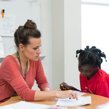 woman sitting at a desk helping a young female student with her classwork