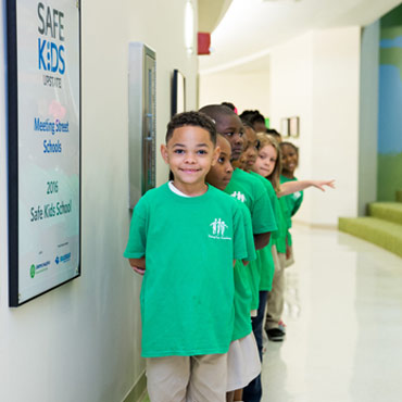 smiling children standing in a neat single file line