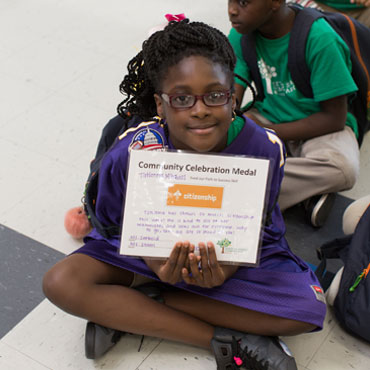 female student holding up an award certificate
