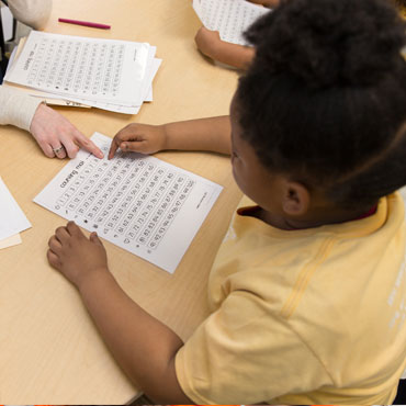 female student sitting at her desk with a worksheet
