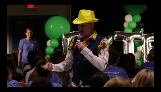 man in a bright yellow hat speaking into a microphone