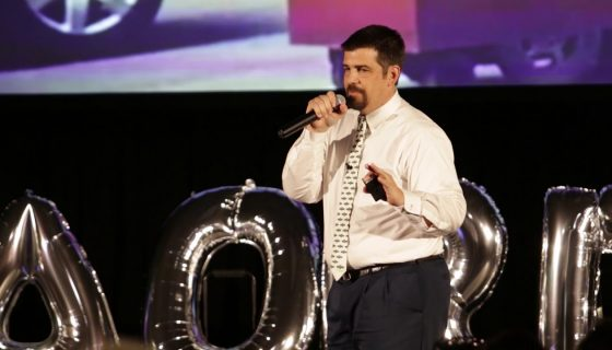 Man on stage speaking into a microphone