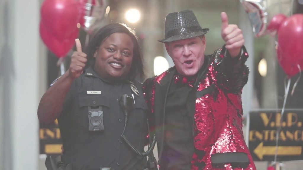 policewoman and a man in a bright red costume posing together giving a thumbs up