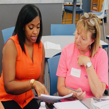 Female teacher in an orange shirt reviewing a document with a woman in a pink shirt