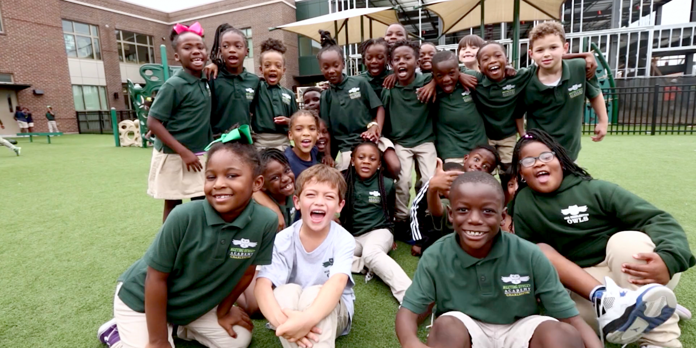large group of students sitting on the playground smiling