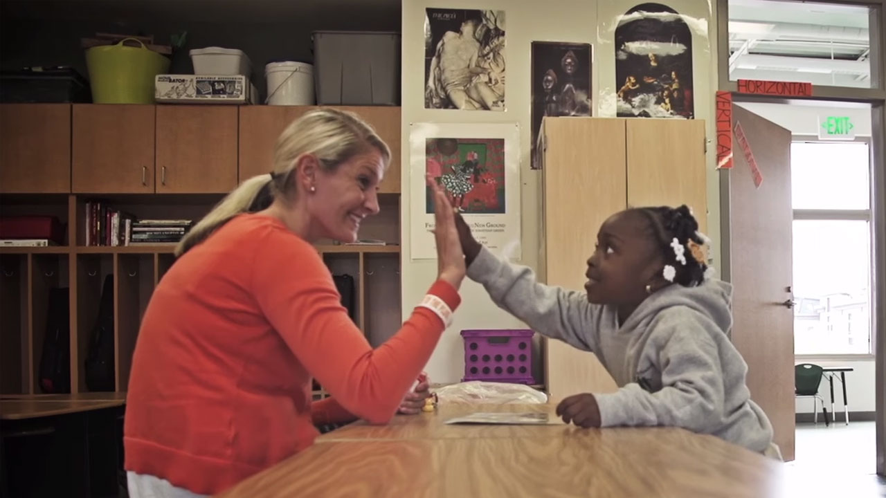 A female teacher sitting in a classroom gives a young student a high five