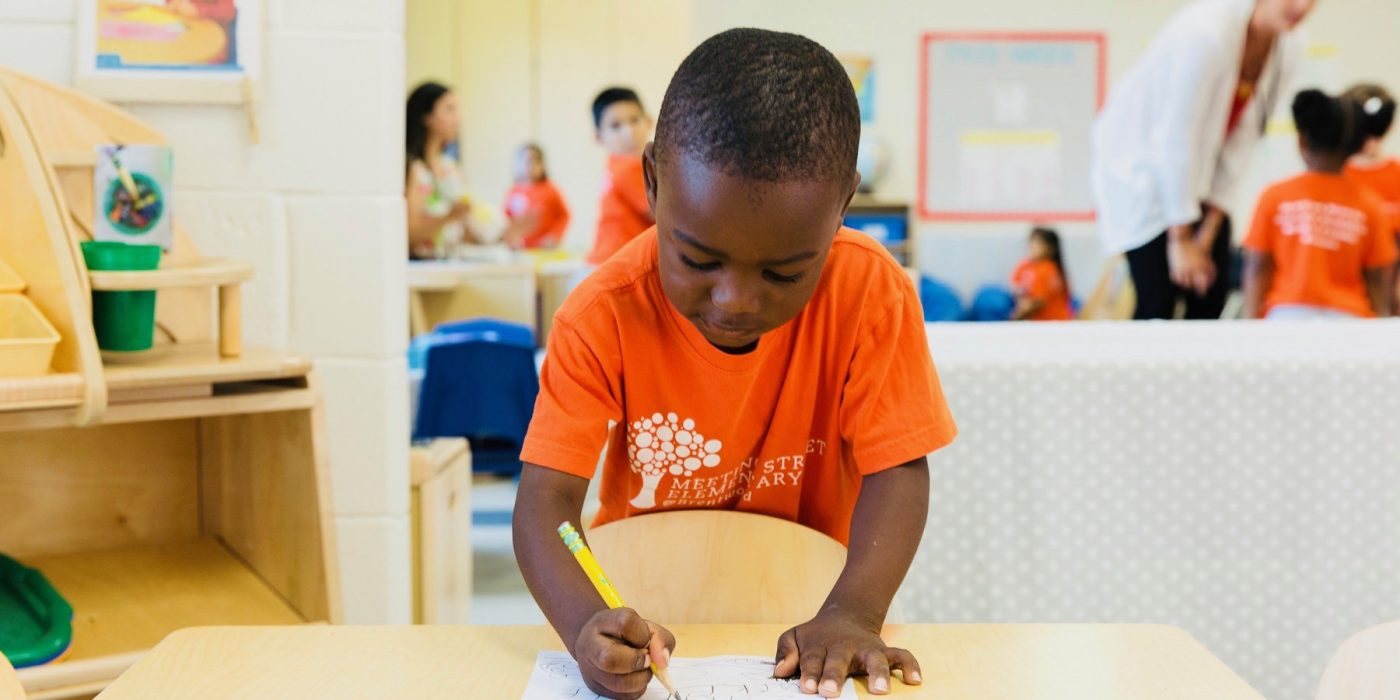 boy standing at desk in a bright orange shirt writing