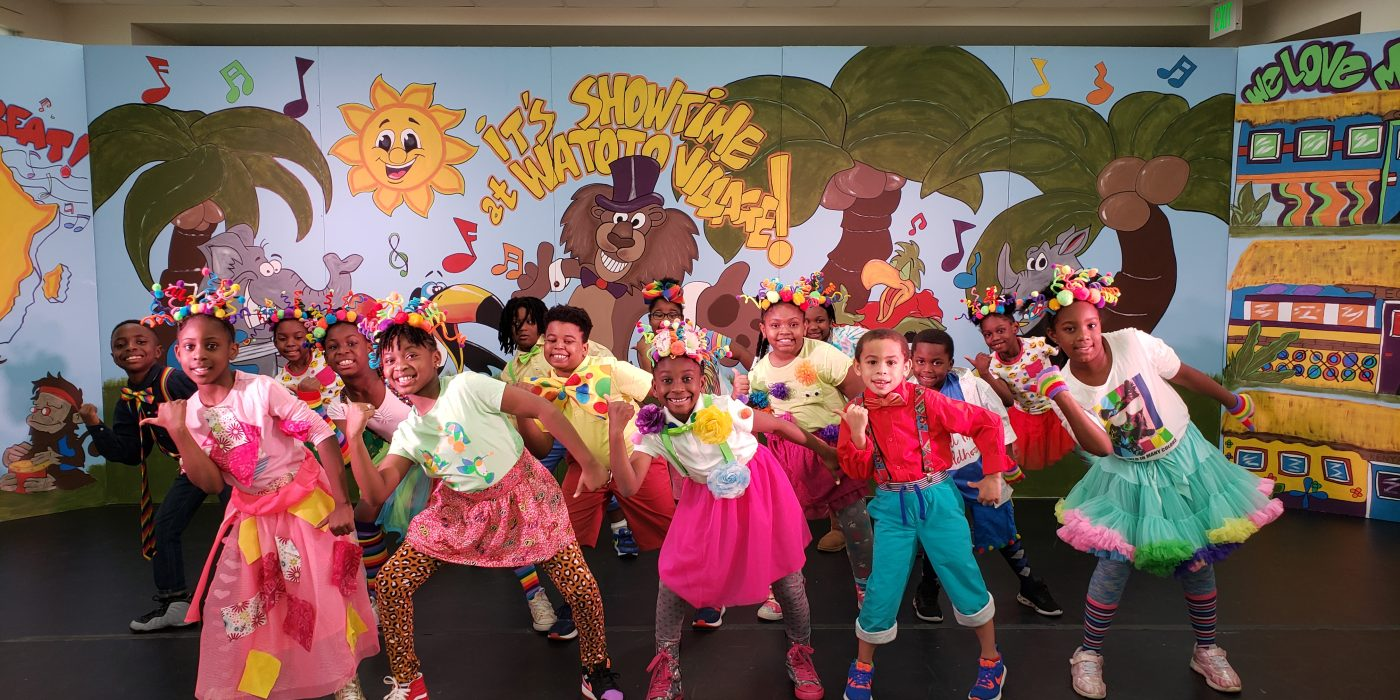 group of fifteen students dressed in vibrant costumes performing a dance routine